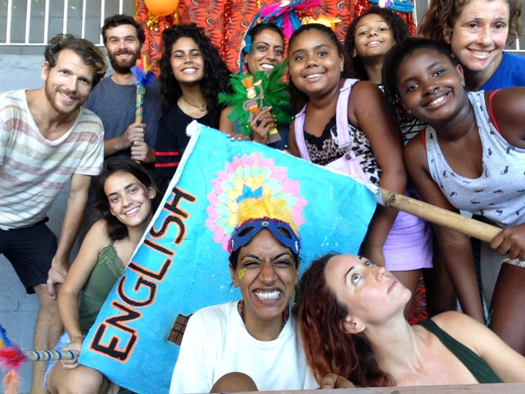 Participants on EduMais's 2018 Summer Camp and their volunteer English teachers hold a flag saying English on it