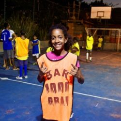 Smiling young girl on football field in favela at night