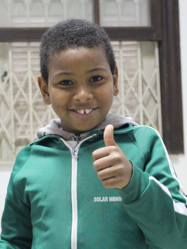 EduMais student gives a thumbs up and smile to the camera