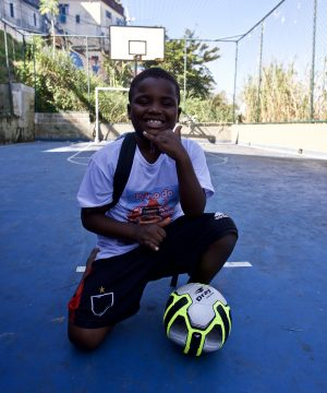 Student on EduMais's Education-Football Program knees on the pitch smiling with a soccer ball in front of him