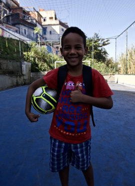 Student on EduMais's Education-Based football program holds a ball under his arm after receiving it as a donaion from Wings with favela in background