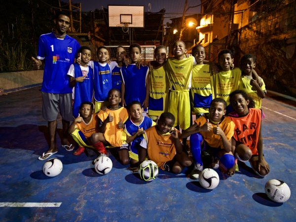 EduMais football program leader William with 15 of his students on the pitch at night and five soccer balls