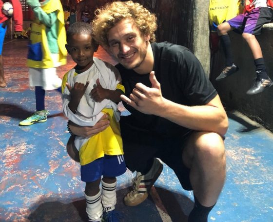 EduMais football volunteer Mads poses with the program's youngest student, who is about a third of his size