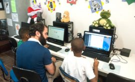 EduMais Web Design Program volunteer Felipe teaches two boys how to build their websites