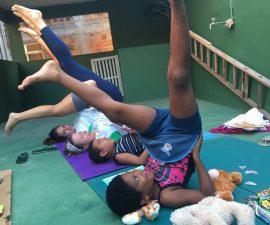 EduMais volunteer teachers Hannah and Matylda show students how to do yoga on EduMais's after-school program
