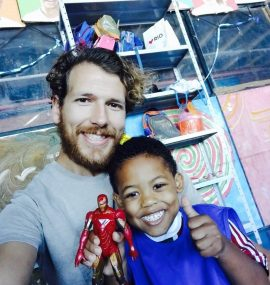 EduMais volunteer Tim with student making a thumbs up and holding an Iron Man toy
