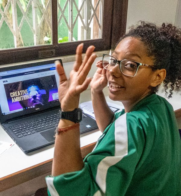 EduMais student Thais waves to the camera while designing a website on our Web Design course