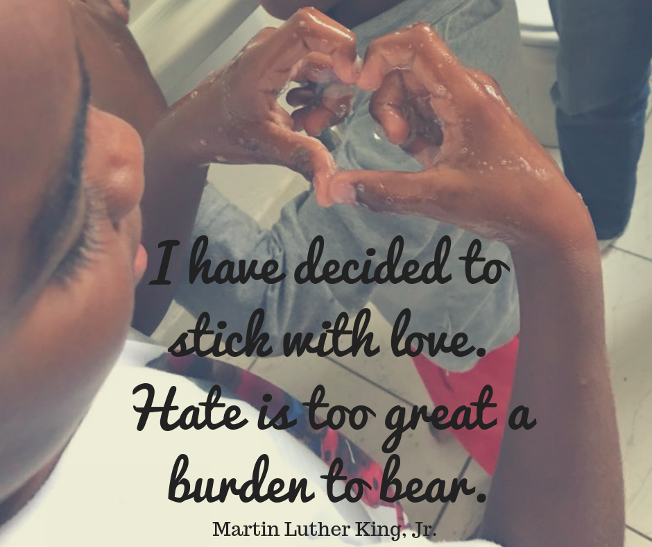 After-school student forms a heart with washing up liquid bubble in his hands and Martin Luther King Jr quote about love overlaid