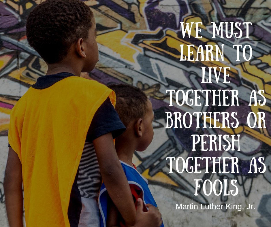 EduMais football student with arm around younger boy and Martin Luther King quote about need to learn to live together
