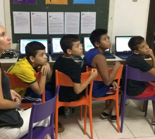 Four boys on EduMais's Programming Camp in front of their computers and with volunteer Audrey looking at whiteboard