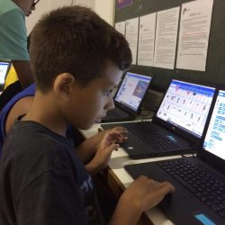Boys on EduMais's Game Design Camp looking intently at their computers
