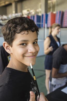 Kid with pencil in winter camp in favela in Rio de Janeiro